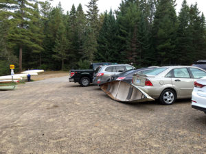 Canoe leaning against car at Rock Lake access point in Algonquin Park