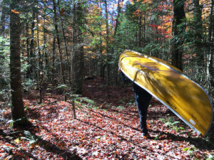 Portaging a canoe during Thanksgiving weekend with leaves on the ground