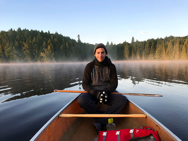 Smiling while sitting in the back of a canoe