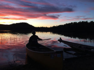 Finishing a solo canoe paddle during a beautiful sunset