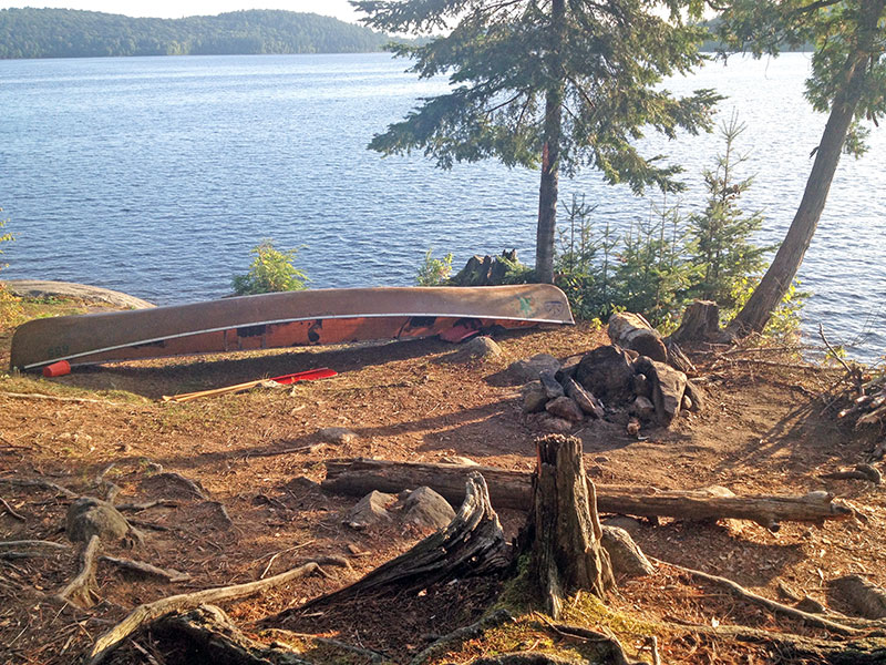 Manitou Lake campsite #5 fire pit area with seating and canoe