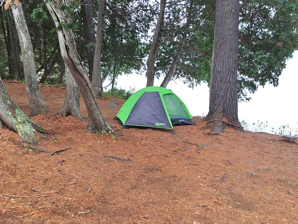 Green Eureka tent pitched on campsite #7 on White Trout Lake
