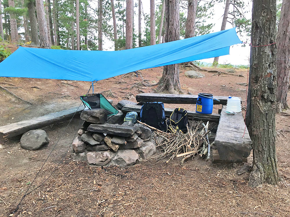 Fire pit and seating with gear and tarp set up on White Trout Lake island campsite