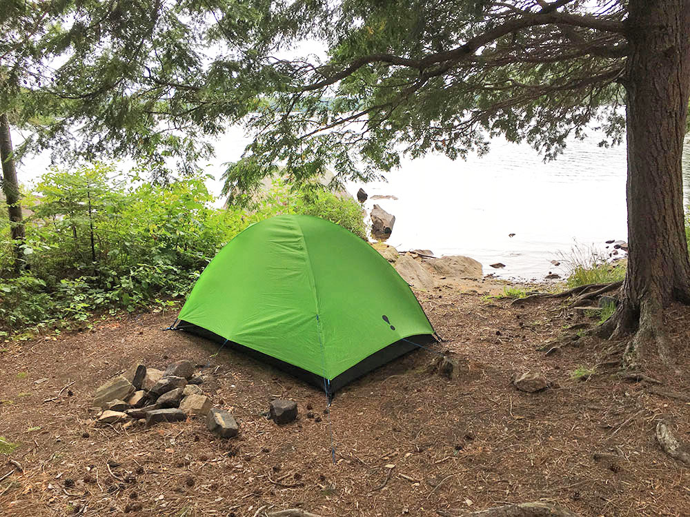 Green tent pitched by the water on campsite #8 on White Trout Lake