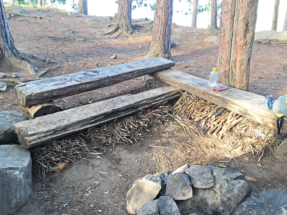 Huge courtesy pile of firewood tucked underneath campsite benches on White Trout Lake
