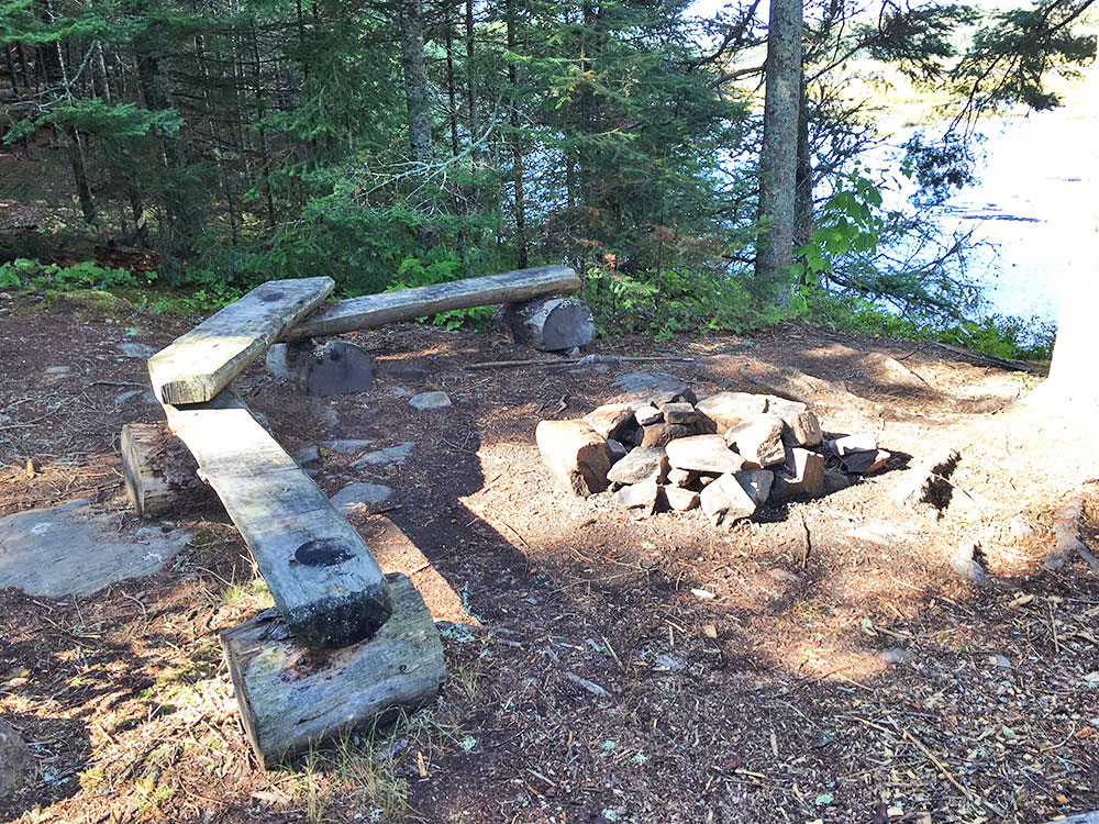 Fire pit and seating area on Grassy Bay campsite