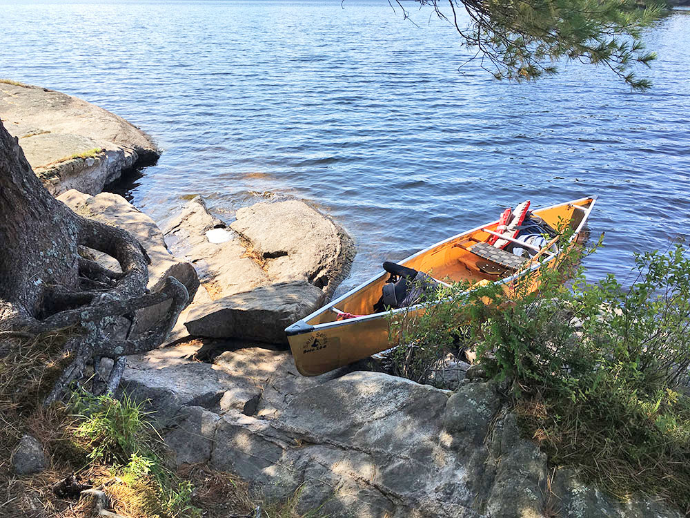 Yellow canoe at rocky shore on McIntosh Lake