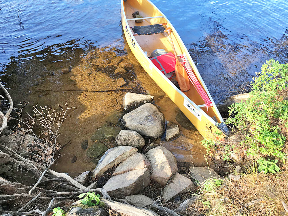 Yellow solo canoe at the landing of campsite #14 on McIntosh Lake in Algonquin Park