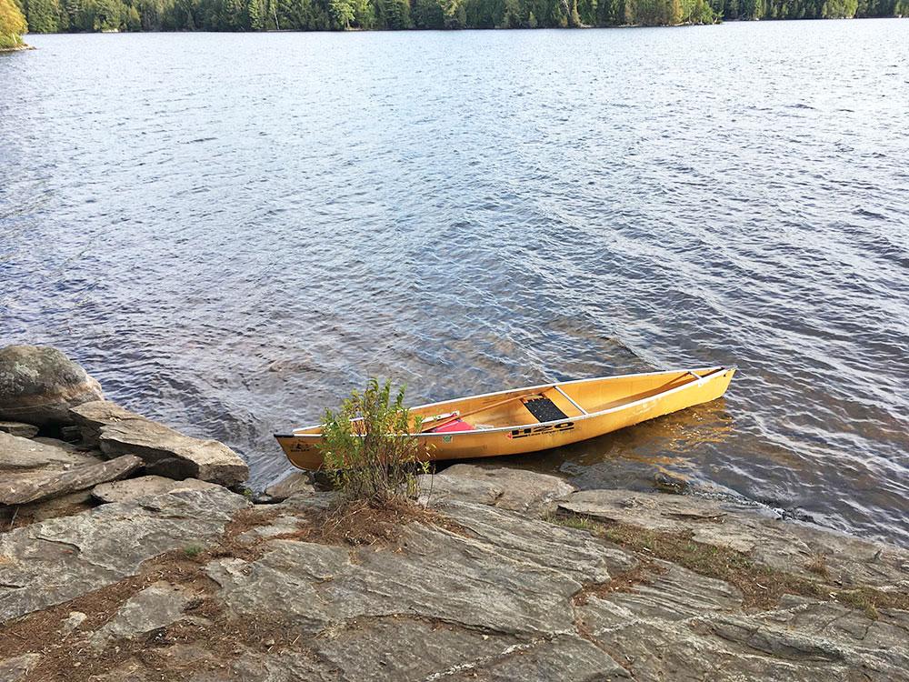 Yellow solo canoe at the rocky canoe landing on McIntosh Lake campsite #11