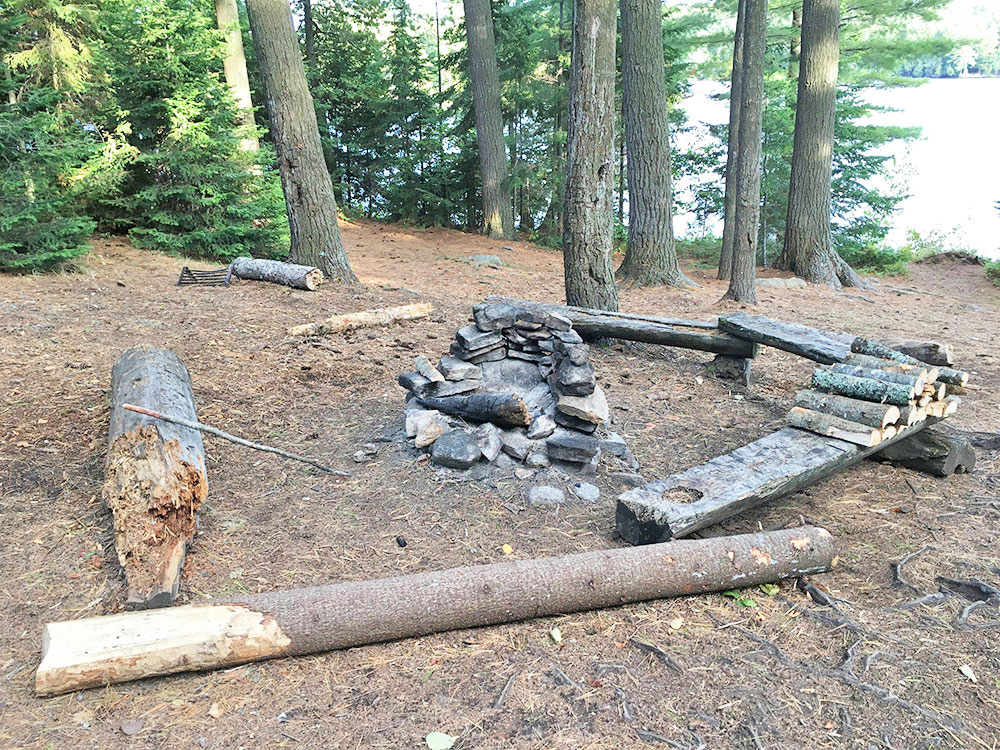 Fire pit and seating area on island campsite on McIntosh Lake