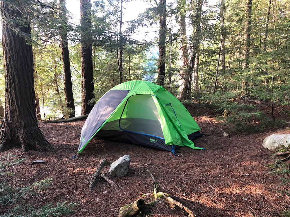 Green Eureka tent pitched on campsite #15 on Lake Louisa