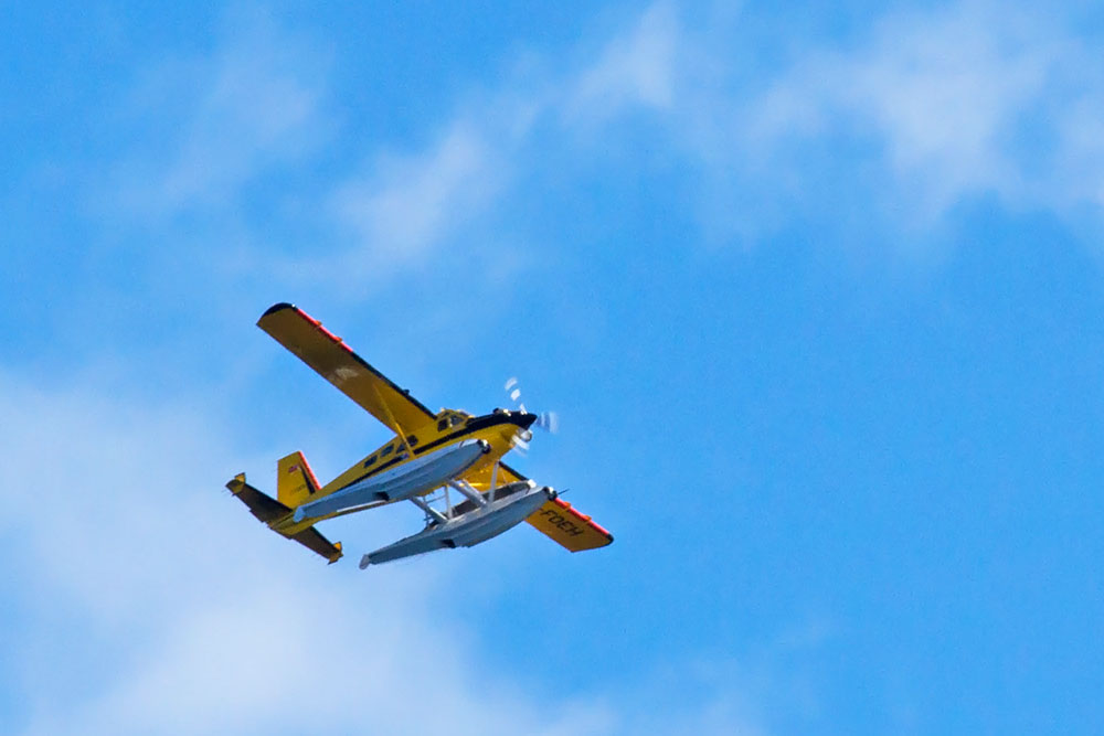 Algonquin Park yellow airplane flying in the sky