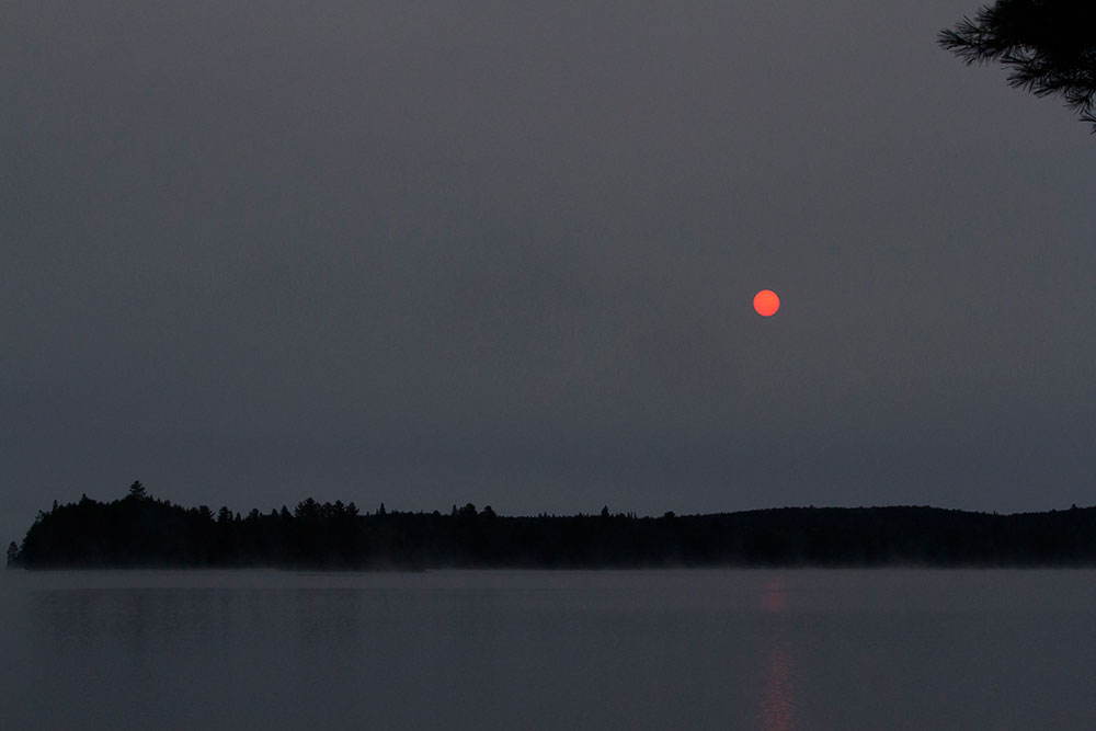 Dark sunrise with bright sun on Big Trout Lake in September 2020