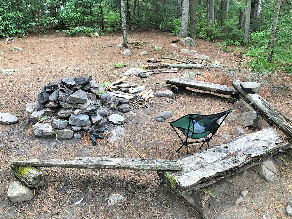 Main fire pit and seating area on Big Trout Lake island campsite #11 in Algonquin Park