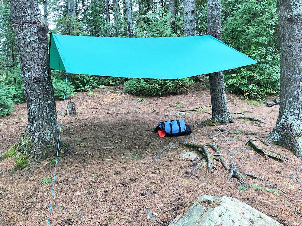 Green Aqua Quest tarp pitched above tent spot on Big Trout Lake campsite #11 island
