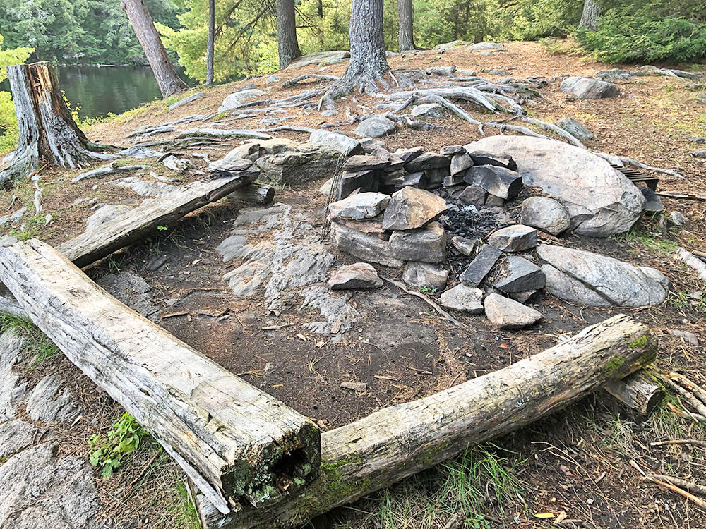 Fire pit with flat benches for seating on Campsite #13 on Big Trout Lake