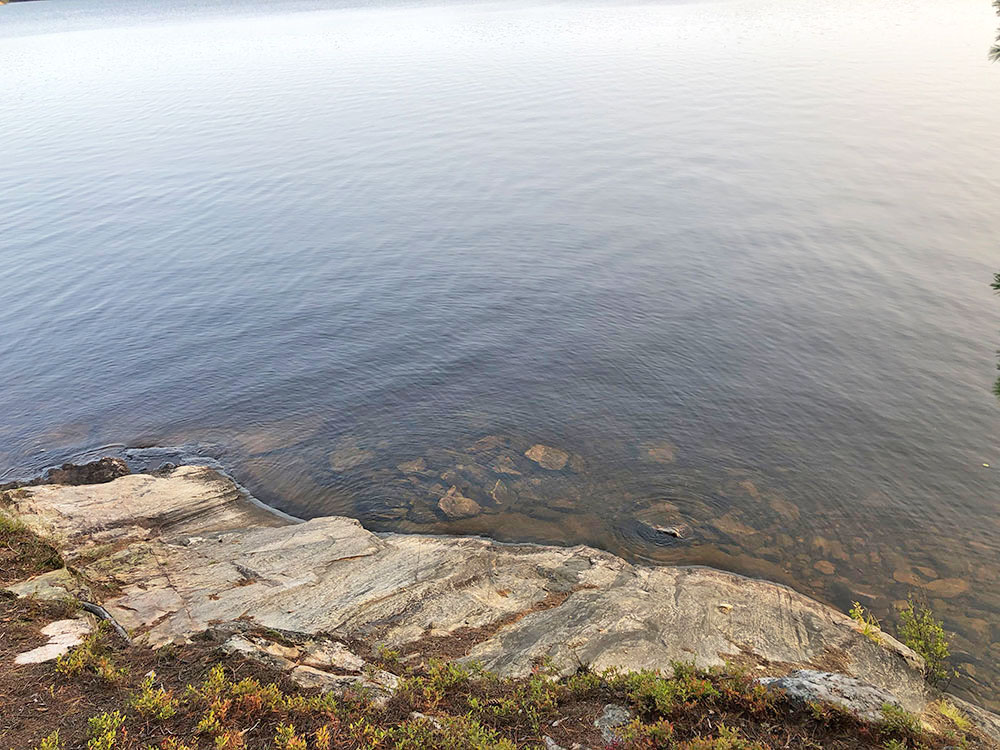 Shallow waters in front of rocky shoreline on campsite #13 on Big Trout Lake