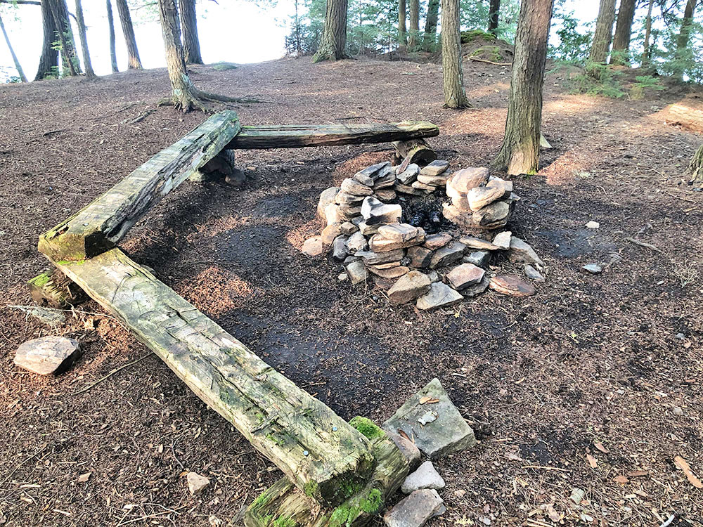 Fire pit with three flat benches for seating on Campsite #15 on Big Trout Lake