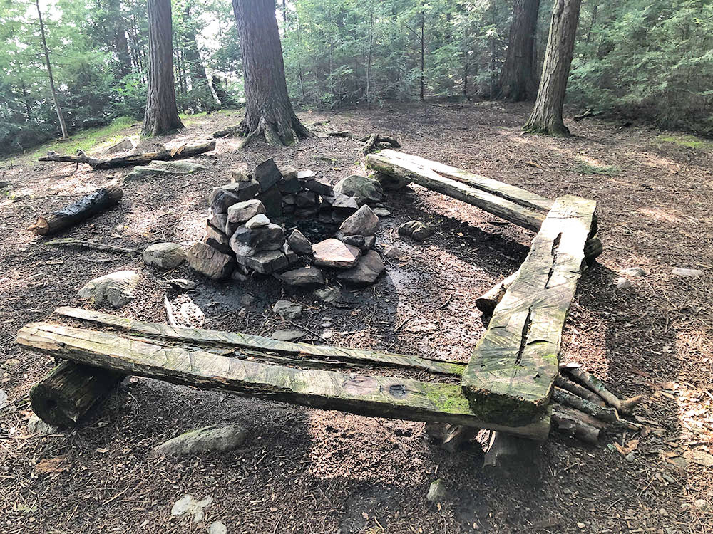 Fire pit with flat benches for seating on Big Trout Lake Campsite #16