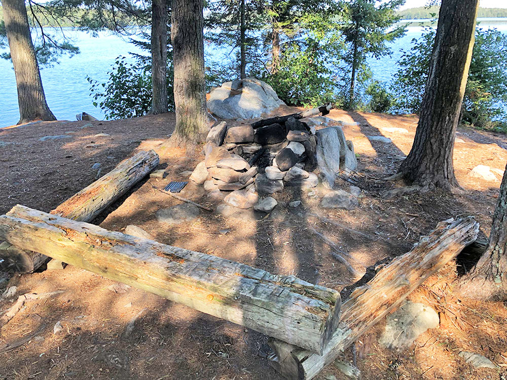 Fire pit with flat seating surrounding it on Big Trout Lake campsite #22