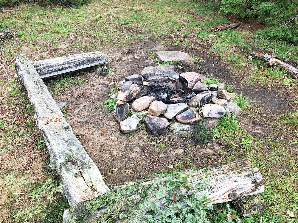 Small fire pit with 3 benches of seating surrounding it on Big Trout Lake campsite 3