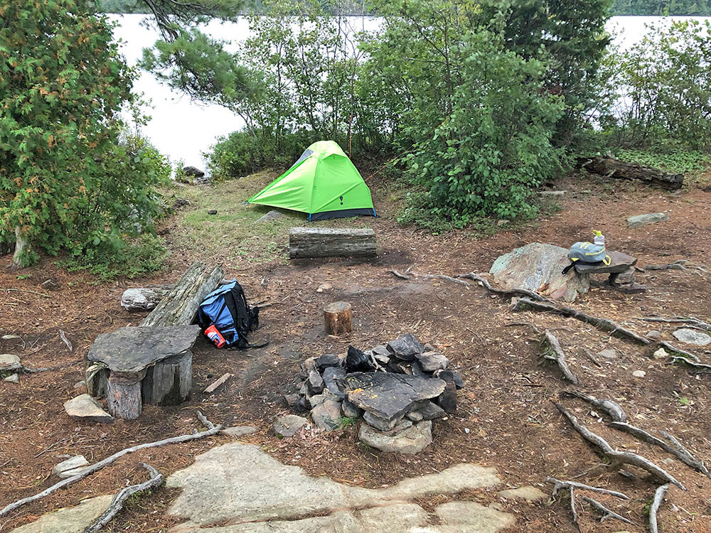 Interior of campsite with tent pitched before fire pit area on Burntroot Lake