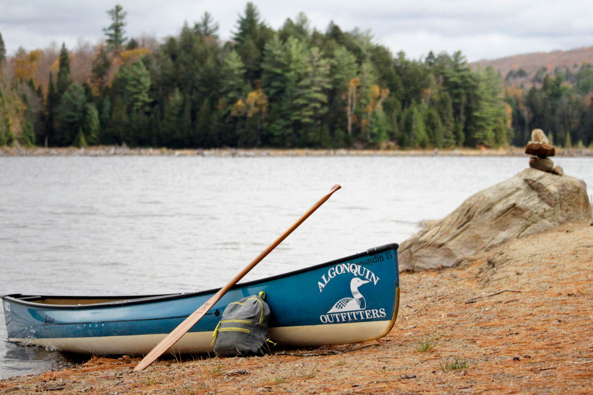 Blue Keewaydin canoe with daypack and paddle learning on it, Ragged Lake south island campsite beach