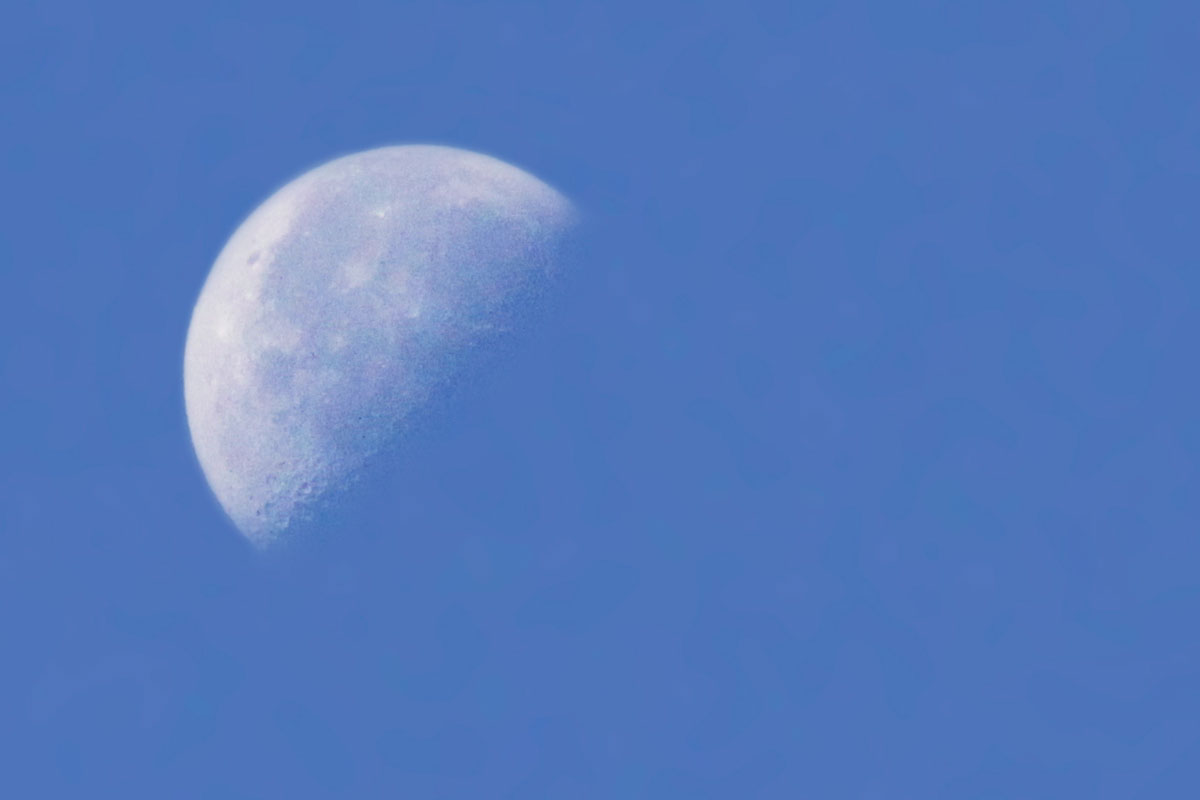 Half moon over Ragged Lake campsite with blue sky