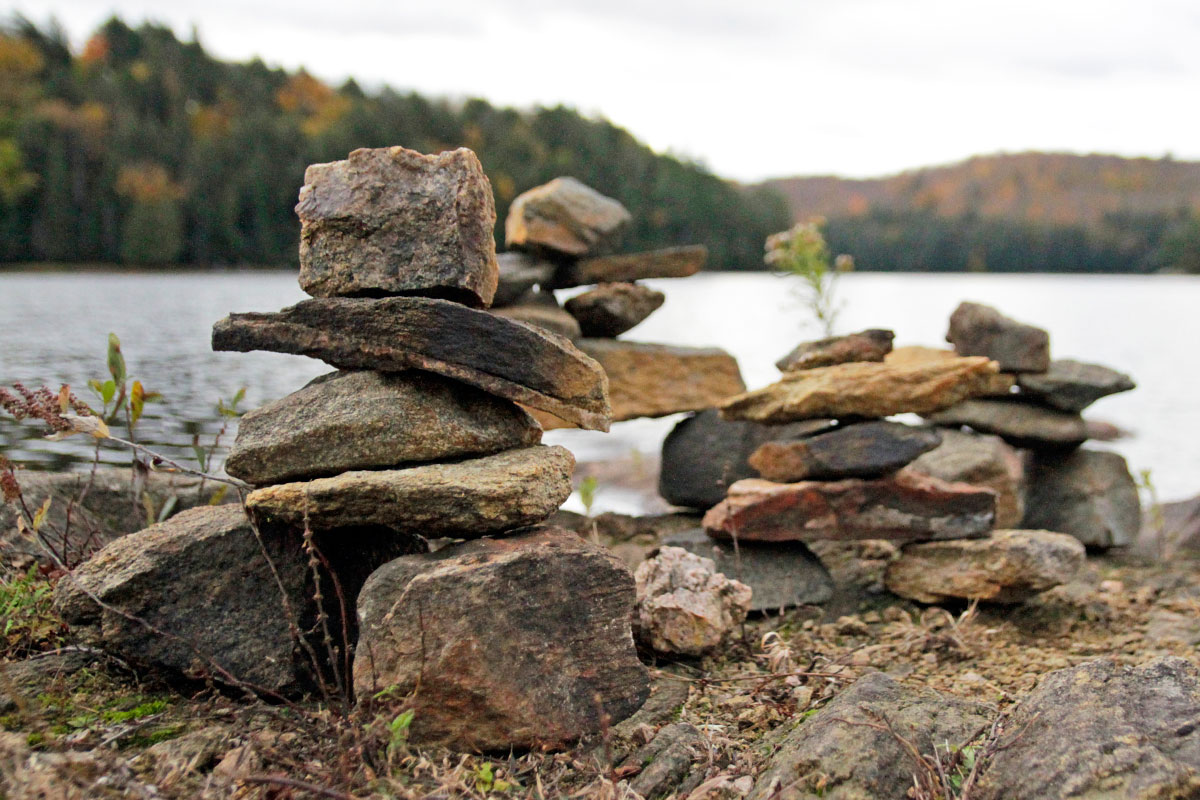Inukshuk on Ragged Lake campsite with fall colour trees in the background