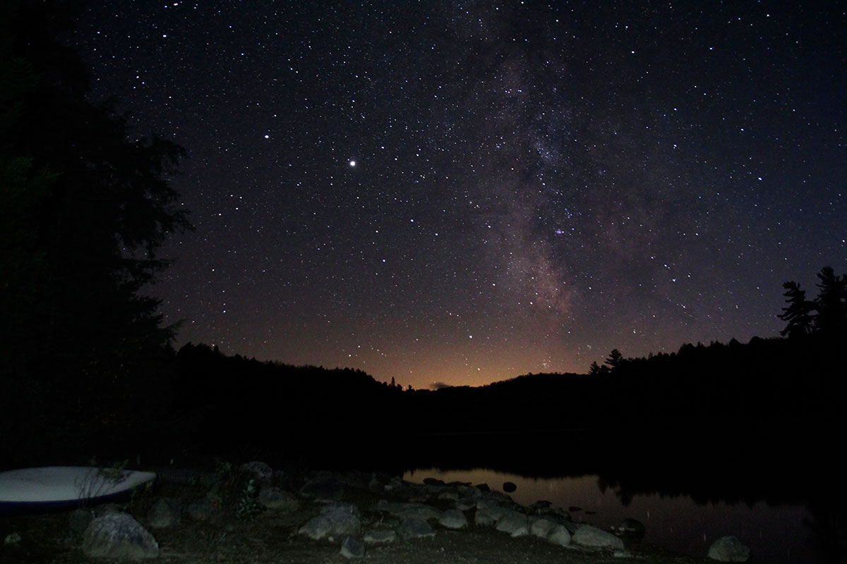 Milky way night sky photography in Algonquin Park on Ragged Lake with canoe