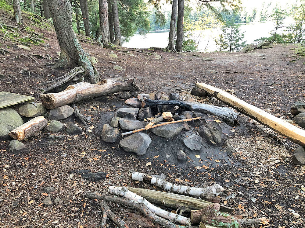 Fire pit and seating area on Ragged Lake campsite #13