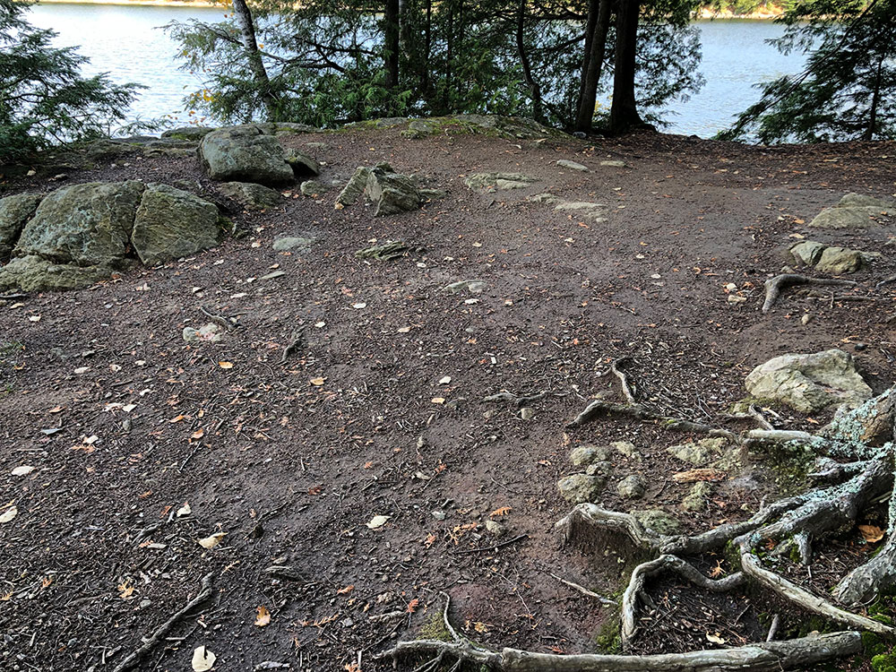Small tent spot with small rocks surrounding it on Ragged Lake campsite #13