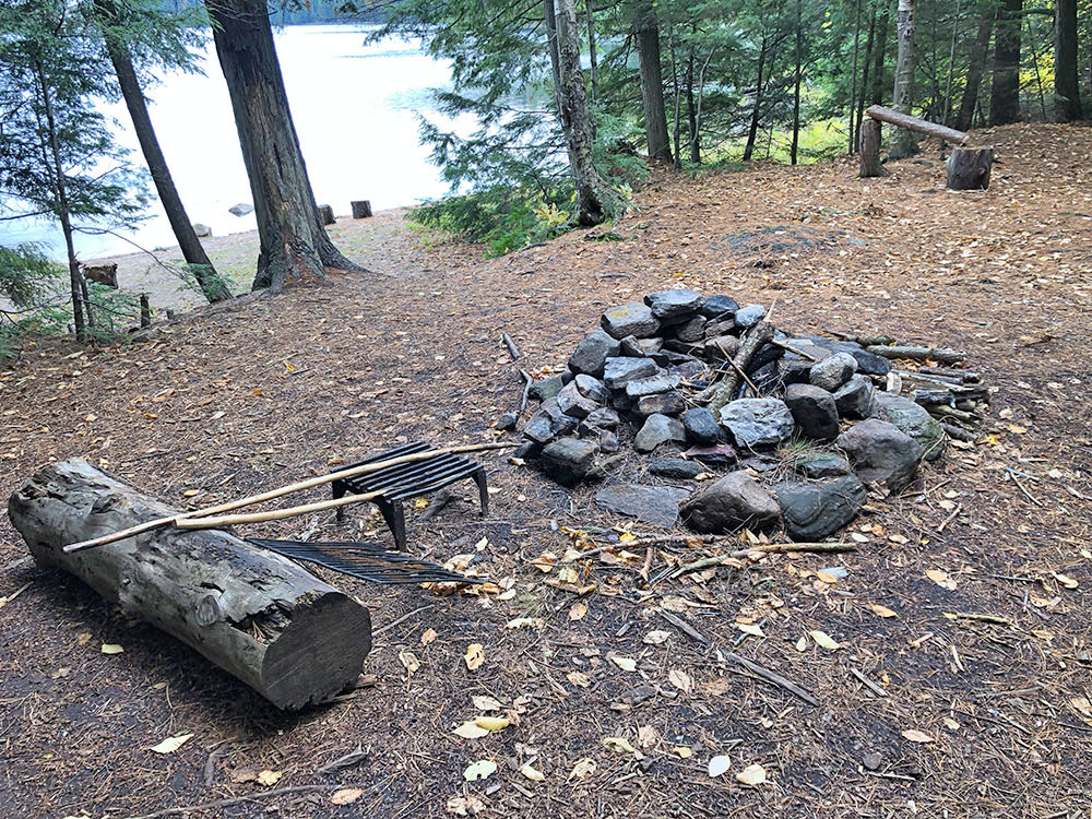 Fire pit and seating area on Ragged Lake campsite #14 in Algonquin Park