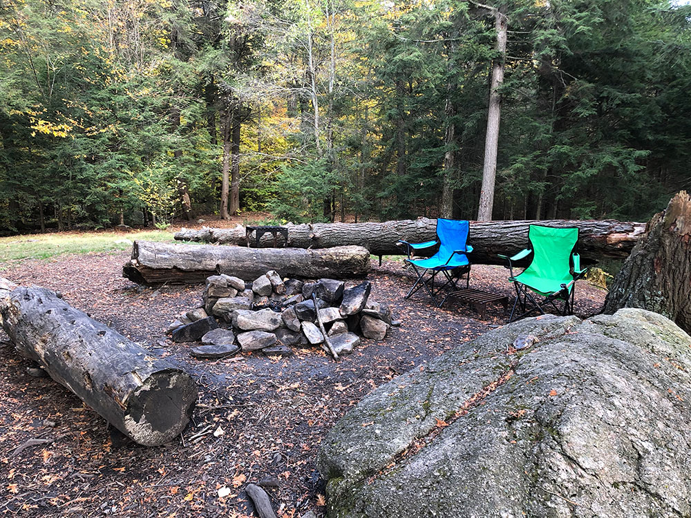 Fire pit and seating area for Ragged Lake campsite with blue and green lawn chairs