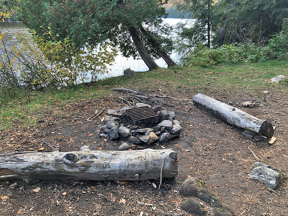 Main fire pit and seating area on Ragged Lake campsite #21