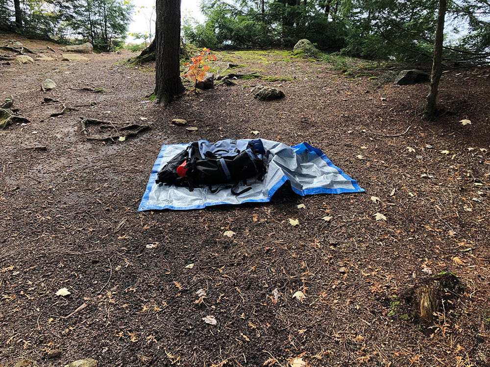 Tent spot on Ragged Lake campsite with tarp and gear laid out