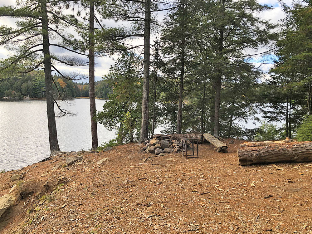 Campsite #9 on Ragged Lake facing the fire pit and seating area
