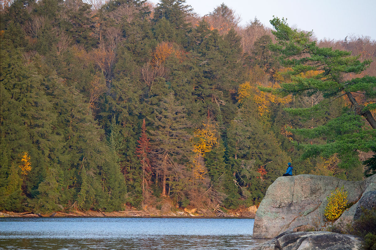 Woman in blue jacket sitting on Ragged Lake campsite observing early morning on Ragged Lake