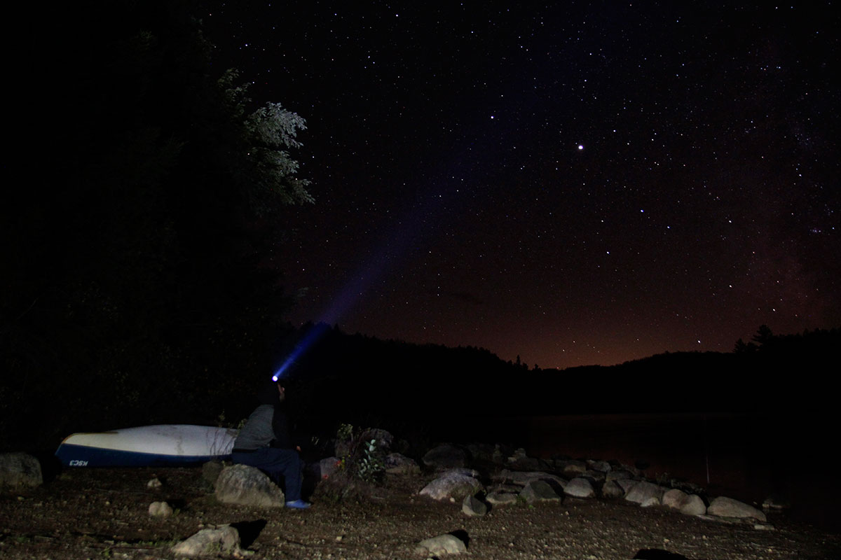 Sitting beside solo canoe shining headlamp at starry night sky in Algonquin Park