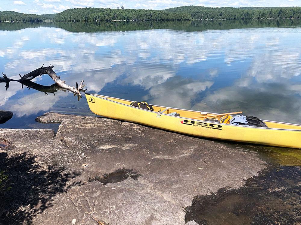 Ralph Bice Campsite 13 Algonquin Park rocky canoe landing with yellow solo canoe