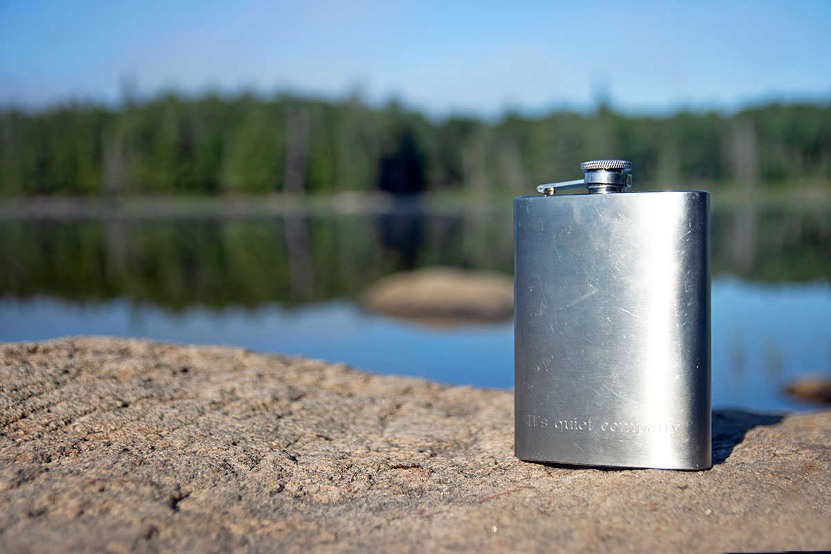 Whiskey flask on rock on Queer Lake July 2021